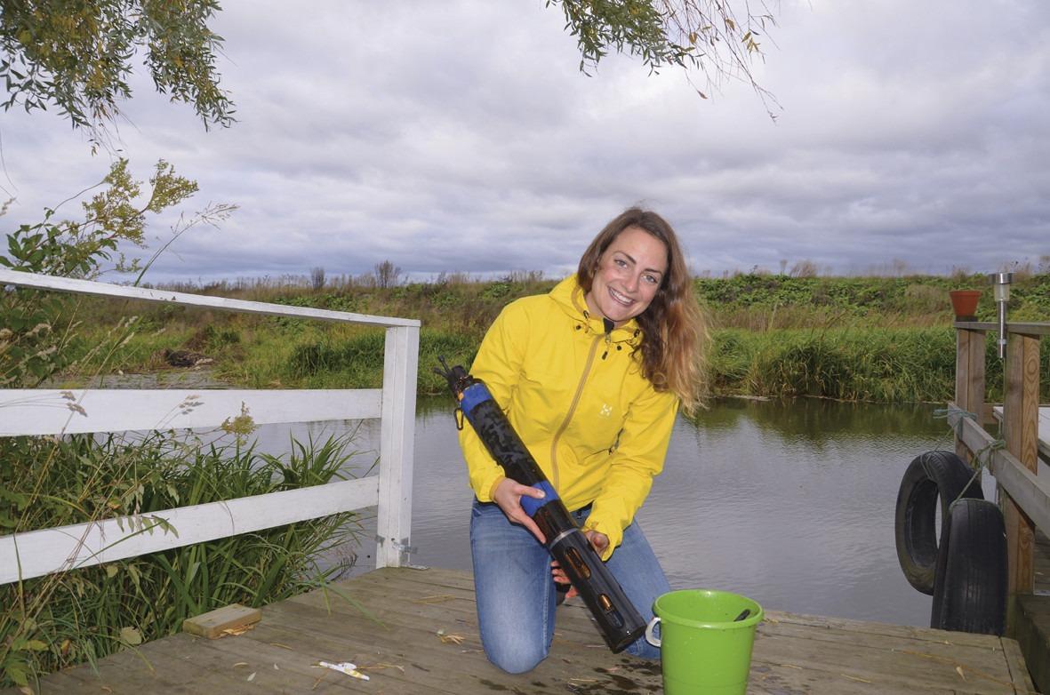 Emma Lannergård rengör en sensor i Sävjaå