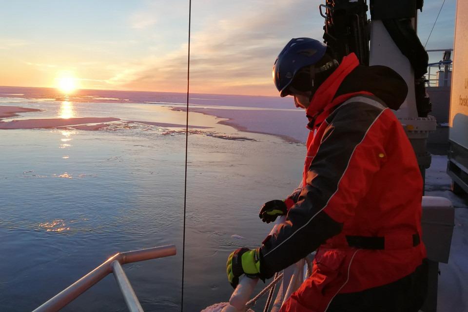 Person tittar ut över havet från relingen på en båt